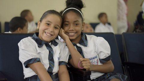 Dos estudiantes del Colegio Villa Carmen sonríen mientras disfrutan de la VI Muestra de Cine Medioambiental en la BIJRD.