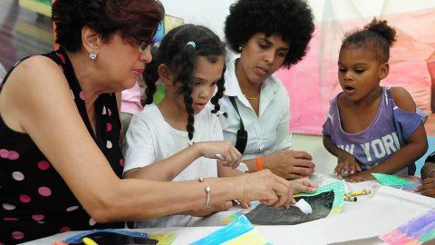La artista plástica Lizette Mejía enseña a los pequeños a utilizar la técnica del rasgado.