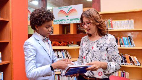 """El actor Jaden Michael entrega un ejemplar de """"Maravillas"""", uno de sus libros favoritos, a la directora de la Biblioteca Infantil y Juvenil República Dominicana (BIJRD), Dulce Elvira de los Santos."""