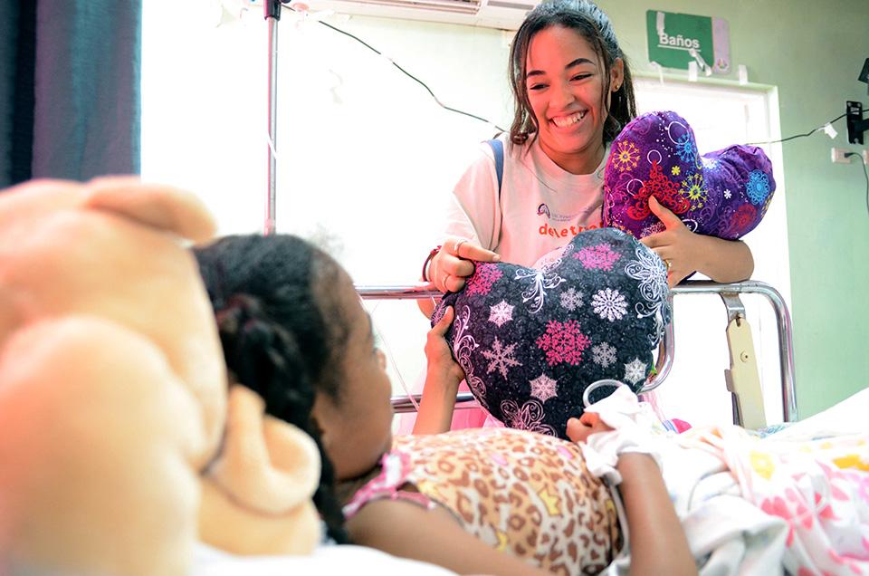 """Una integrante del voluntariado de la Biblioteca Infantil y Juvenil República Dominicana (BIJRD) entrega un cojín en forma de corazón a una niña interna en el Hospital Infantil Dr. Robert Reid Cabral, como parte de la iniciativa """"Corazones Solidarios""""."""